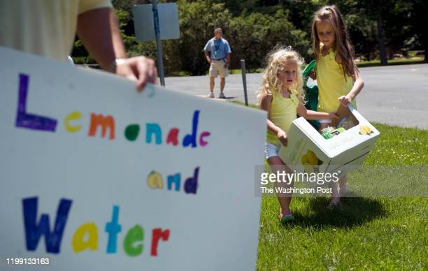 Sofia Fernandez right helps her sister Alina Fernandez move their lemonade stand 50 feet from the corner of River and Harrington Dr on Friday June 17...