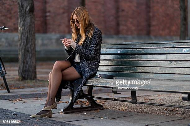 Sofia Grau Fashion Blogger and owner of SCIC Swimwear @shecomesincolors sitting on a bench writting a text message wearing a black plaid checked...