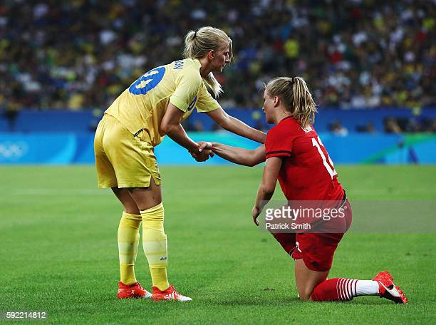 Sofia Jakobsson of Sweden helps Tabea Kemme of Germany to her feet during the Women's Olympic Gold Medal match between Sweden and Germany at Maracana...