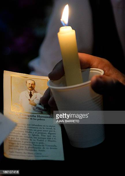 Sofia Miselem A man holds a card bearing an image of late doctor Jose Gregorio Hernandez during a mass at the Holy Church of La Candelaria where his...