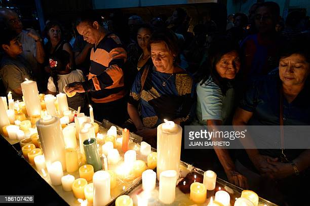 Sofia Miselem People pray and light candles before the tomb of doctor Jose Gregorio Hernandez during a mass at the Holy Church of La Candelaria in...