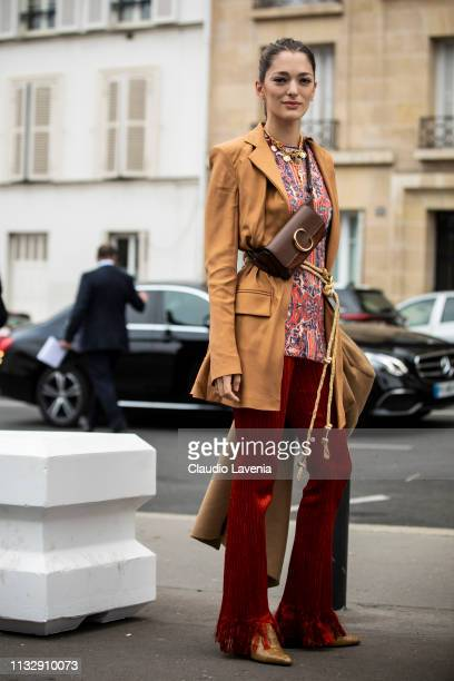 Sofia Sanchez de Betak wearing a printed top tan blazer red trousers beige coat beige mules and Chloe fanny pack is seen outside Chloe on Day 4 Paris...