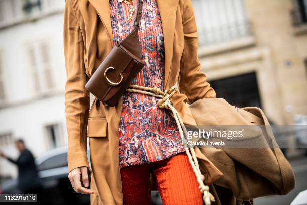 Sofia Sanchez de Betak wearing a printed top tan blazer red trousers beige coat and Chloe fanny pack is seen outside Chloe on Day 4 Paris Fashion...