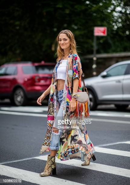 Sofia Sanchez De Betak wearing white cropped top ripped denim jeans ankle boots with snake print Chloe bag with fringes kimono is seen outside Tory...