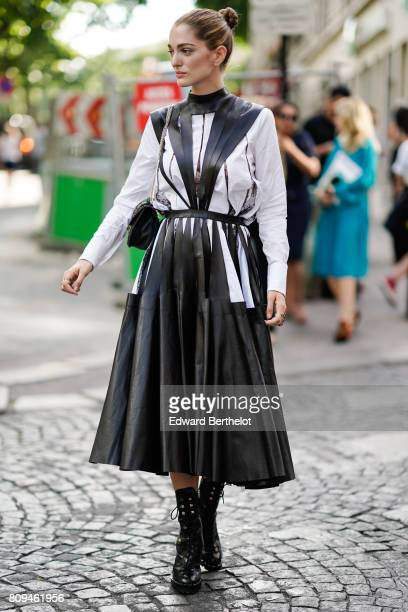 Sofia Sanchez de Betak wears a black and white leather dress with stripes a black bag and black leather boots outside the Valentino show during Paris...