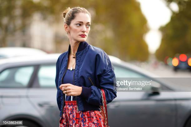 Sofia Sanchez de Betak wears a blue Valentino bomber jacket a red bag a red skirt with printed patterns outside Valentino during Paris Fashion Week...