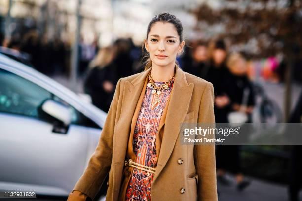 Sofia Sanchez de Betak wears a brown long jacket a necklace a multicolor geometric pattern print top a Chloe bag outside Chloe during Paris Fashion...