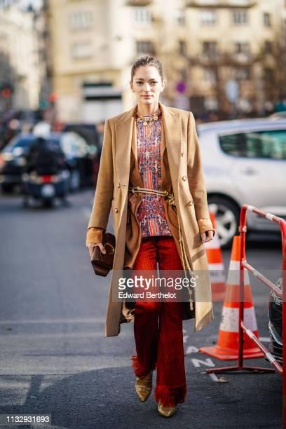 Sofia Sanchez de Betak wears a brown long jacket a necklace a multicolor geometric pattern print top red flared pants snake print shoes a Chloe bag...