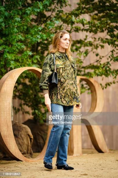 Sofia Sanchez de Betak wears a military camouflage print jacket, a black bag, blue jeans, outside Dior during Paris Fashion Week - Womenswear Spring...