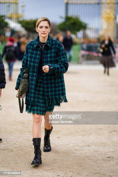 Sofia Sanchez de Betak wears a navy blue top, a golden necklace, a green checked fringed oversized jacket, a skirt, a khaki bag, black leather boots,...