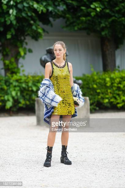 Sofia Sanchez de Betak wears silver earrings, gold chain pendant necklace, a black tulle with yellow / gold shiny sequins embroidered tank-top short...
