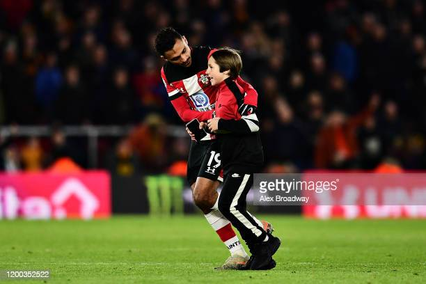 Sofiane Boufal of Southampton escorts a young pitch invader from the pitch during the Premier League match between Southampton FC and Wolverhampton...
