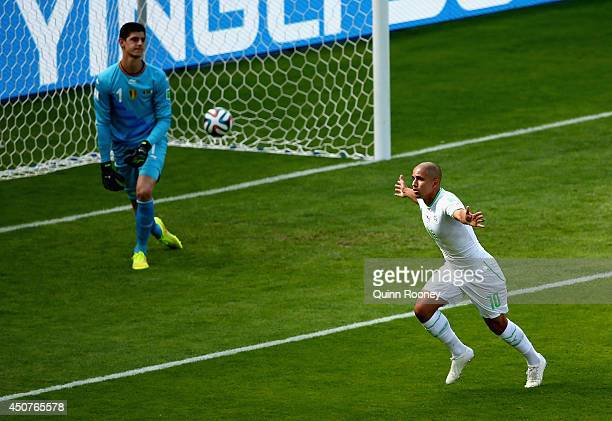 Sofiane Feghouli of Algeria celebrates scoring his team's first goal on a penalty kick past Thibaut Courtois of Belgium during the 2014 FIFA World...