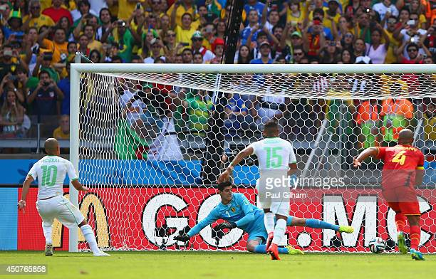 Sofiane Feghouli of Algeria scores his team's first goal on a penalty kick past Thibaut Courtois of Belgium during the 2014 FIFA World Cup Brazil...