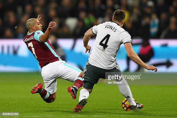 Sofiane Feghouli of West Ham United challenges Phil Jones of Manchester United leading to his sending off during the Premier League match between...
