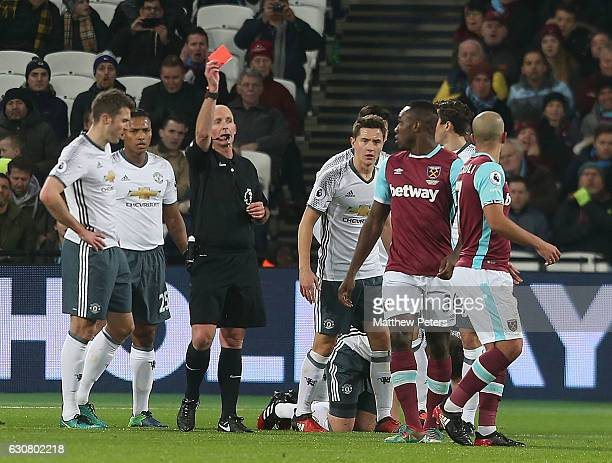 Sofiane Feghouli of West Ham United is sent off by referee Mike Dean for a foul on Phil Jones of Manchester United during the Premier League match...
