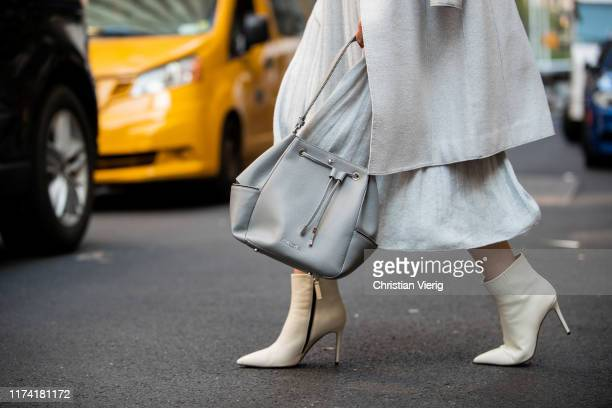 Sofie Valkiers is seen wearing total look Marc Cain light blue pleated dress and wool coat belt bag ankle boots during New York Fashion Week...