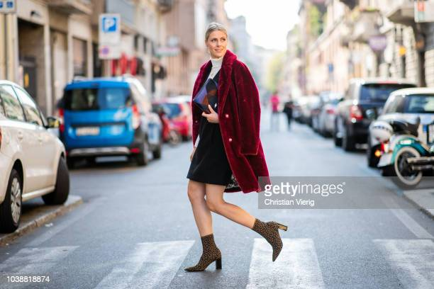 Sofie Valkiers wearing clutch, red coat, white turtleneck, black dress, animal print ankle boots all Marc Cain seen during Milan Fashion Week...