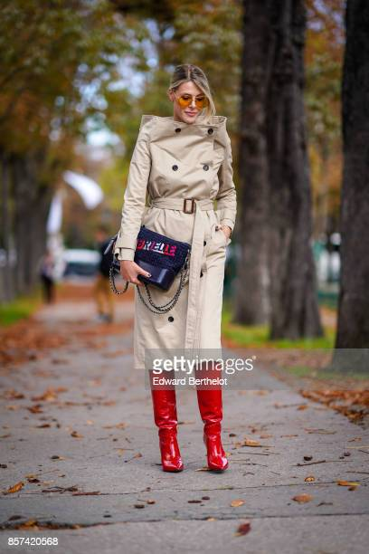 Sofie Valkiers wears a trench coat a bag red boots outside Moncler during Paris Fashion Week Womenswear Spring/Summer 2018 on October 3 2017 in Paris...