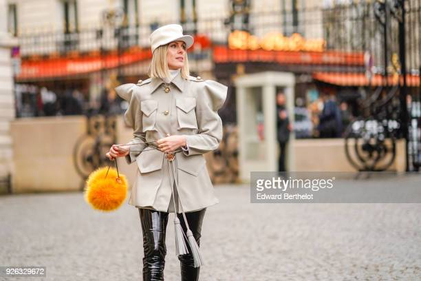 Sofie Valkiers wears a white cap a white jacket black leather thigh high boots a yellow pom pom bag and attends the Nina Ricci show as part of the...