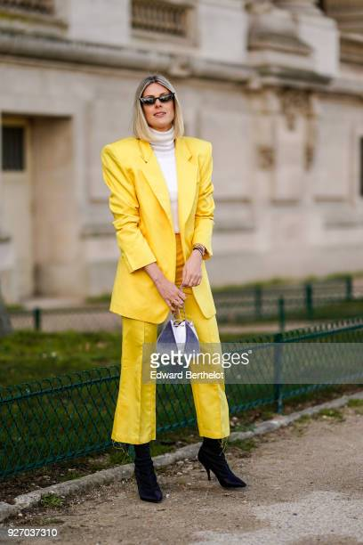 Sofie Valkiers wears a yellow blazer jacket yellow flare cropped suit pants black shoes a turtleneck top during Paris Fashion Week Womenswear...