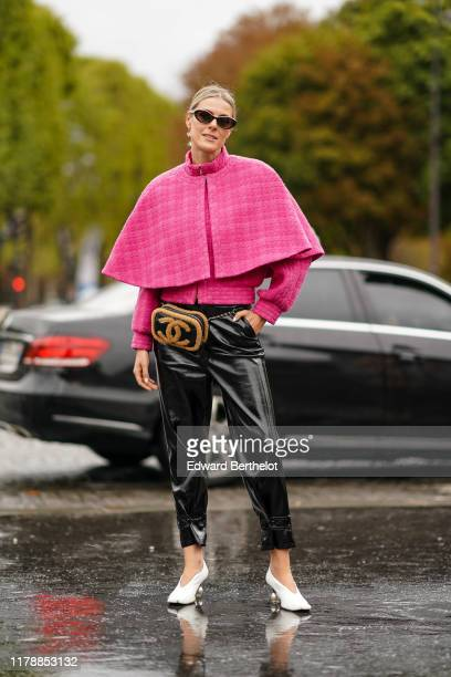 Sofie Valkiers wears sunglasses, a pink cape, a Chanel fluffy brown and black bag, black shiny pants, white shoes, outside Chanel, during Paris...