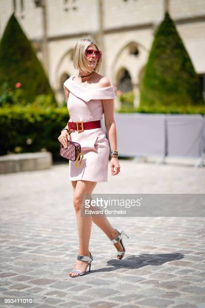 Sofie Valkiers wears sunglasses a pink dress a Dior clutch a red belt silver shoes outside Dior during Paris Fashion Week Haute Couture Fall Winter...