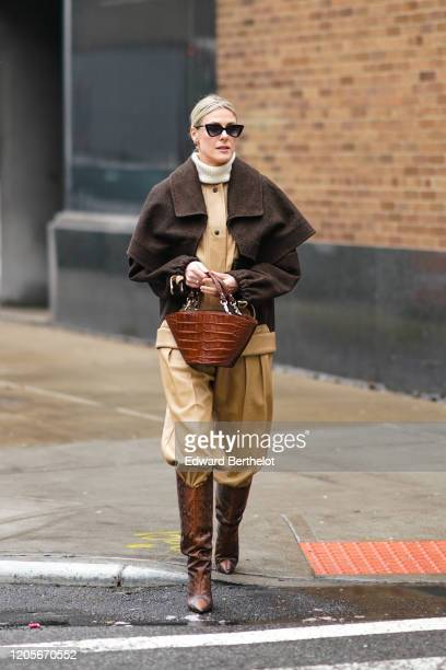 Sofie Valkiers wears sunglasses a white turtleneck pullover a brown jacket a brown leather crocodile pattern bag creamcolor pants brown leather...