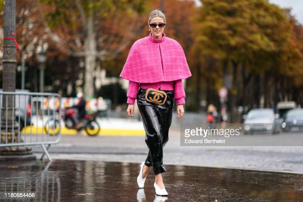 Sofie Valkiers wears sunglasses, earrings, a pink tweed jacket, a pink short cape, a Chanel belt-bag, shiny black patent leather pants, white pointy...