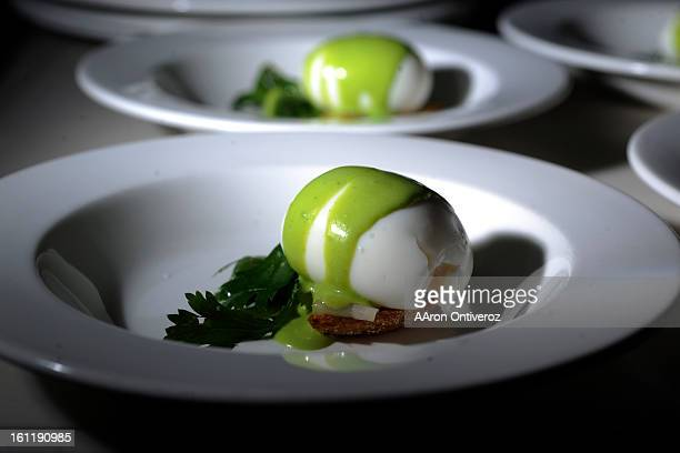 Soft boiled eggs with lardo, edemame and celery leaf pistou are plated before serving during a supper club gathering at Crema Coffee House on Monday,...