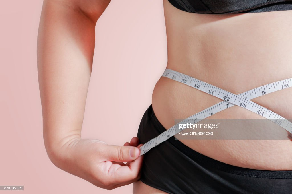soft focus measure your body fat percentage with measuring tape for fat or obesity background : Stock Photo