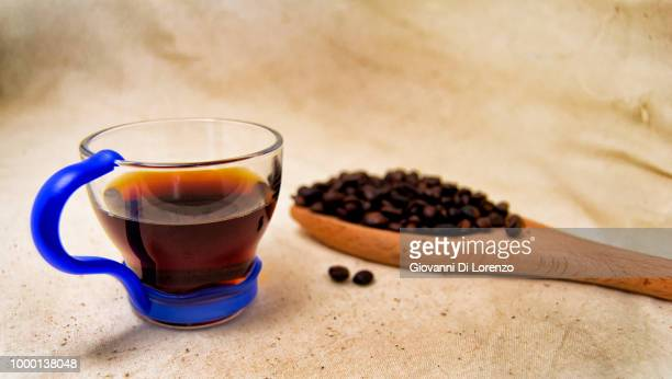 soft focus of a cup of energetic drink infusion and coffee beans on a wooden spoon with a raw...
