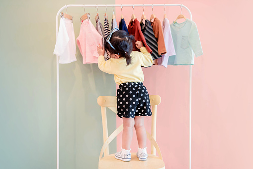 Soft Focus of a Two Years Old Child Choosing her own Dresses from Kids Cloth Rack 931577634