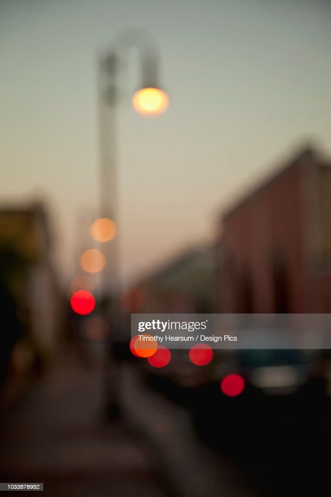 Soft focus view of street scene in the evening with buildings and colourful lights from streetlamp and cars : Stock Photo