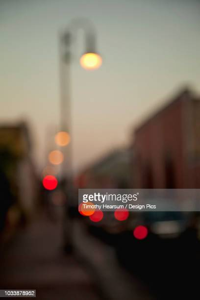 Soft focus view of street scene in the evening with buildings and colourful lights from streetlamp and cars