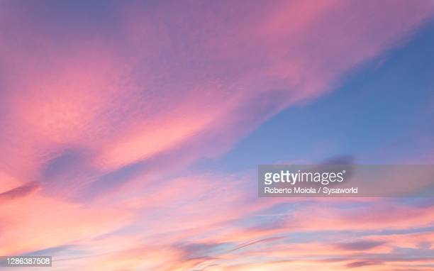soft pink clouds in the sky at sunset - romantic sunset stock pictures, royalty-free photos & images