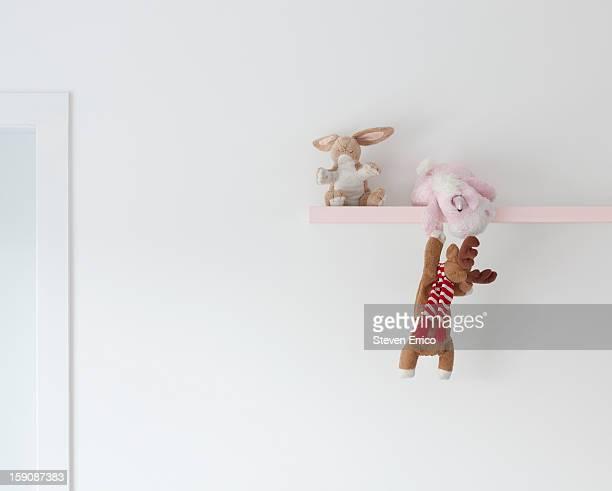 A soft toy unicorn helping a deer up onto a shelf