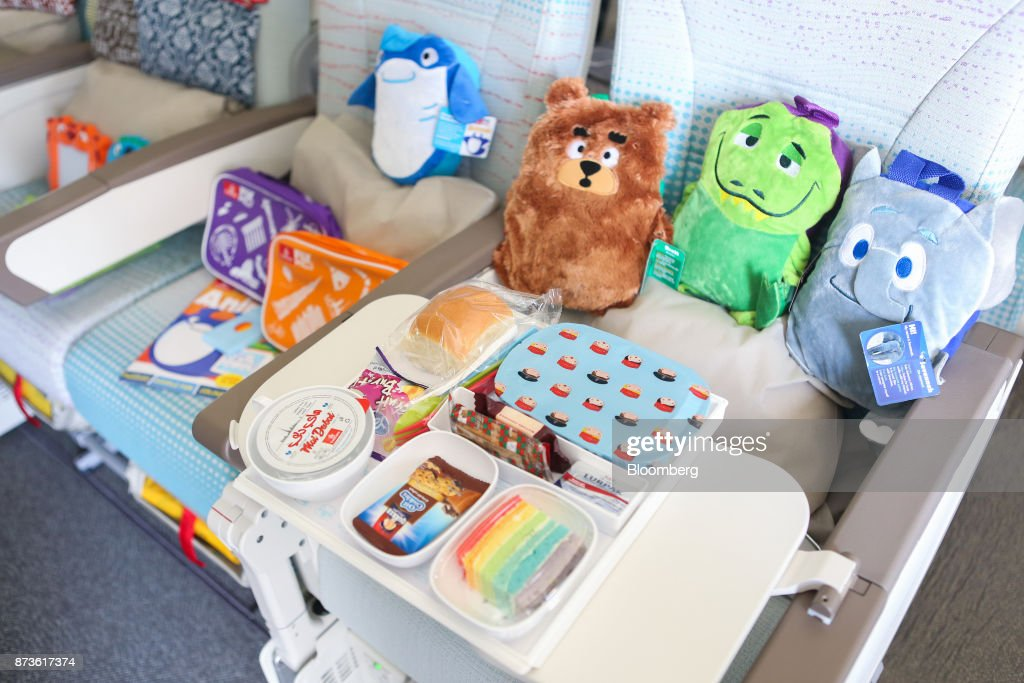 Soft toys and a children's meal sit on a economy class seat on board a Boeing Co. 777 passenger aircraft, operated by Emirates Airlines, during the 15th Dubai Air Show at Dubai World Central (DWC) in Dubai, United Arab Emirates, on Monday, Nov. 13, 2017. The biennial Dubai expo is an important venue for manufacturers to secure deals for their biggest and most expensive jetliners. Photographer: Natalie Naccache/Bloomberg via Getty Images