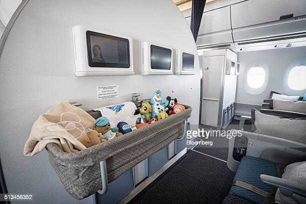 Soft toys sit in a baby bassinet at a bulkhead of the economy class cabin of an Airbus SE A350 aircraft operated by Singapore Airlines Ltd during an...