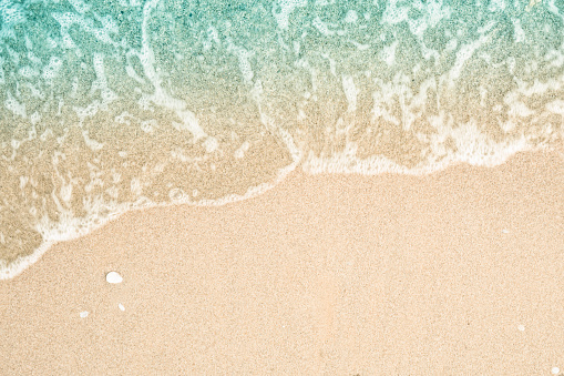Soft wave of turquoise sea water on the sandy beach. Close-up and directly above photographed. 912159594