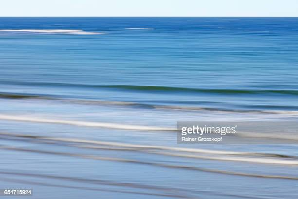 soft waves on ocean beach (blurred) - rainer grosskopf stock pictures, royalty-free photos & images