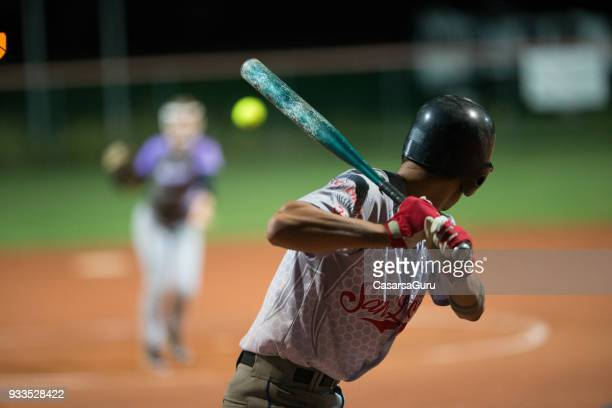softball batter preparing to hit the ball mid air - softball stock pictures, royalty-free photos & images