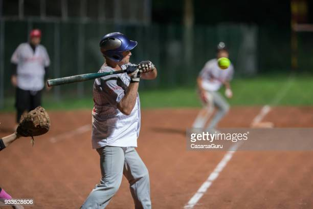 softball batter trying to hit the ball mid air - softball stock pictures, royalty-free photos & images