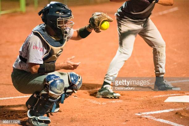 softball catcher catching the ball - baseball catcher stock photos and pictures