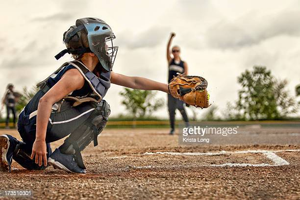 a softball catcher shown catching a pitch - softball stock pictures, royalty-free photos & images