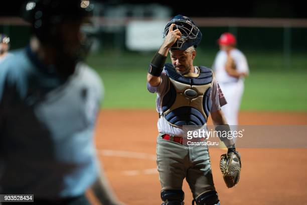 softball catcher taking his helmet off - baseball catcher stock photos and pictures