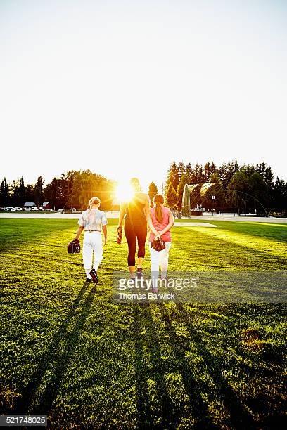 Softball coach walking off of field with players