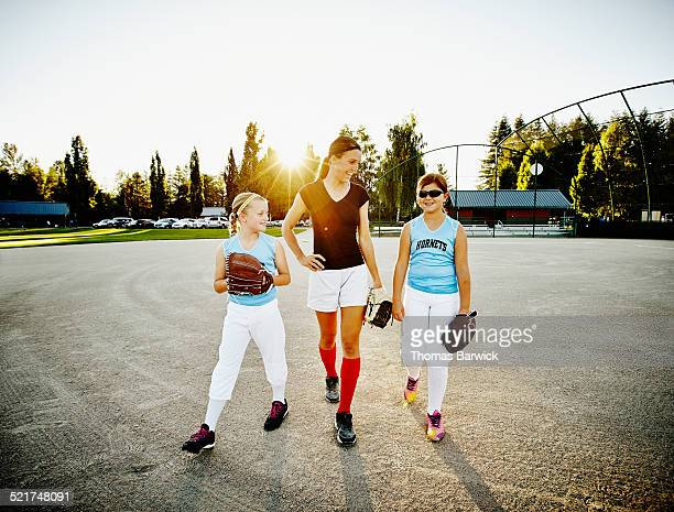 Softball coach walking with two young players
