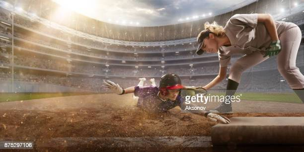 softball female players on a professional arena. baseball 3rd base slide - softball stock pictures, royalty-free photos & images
