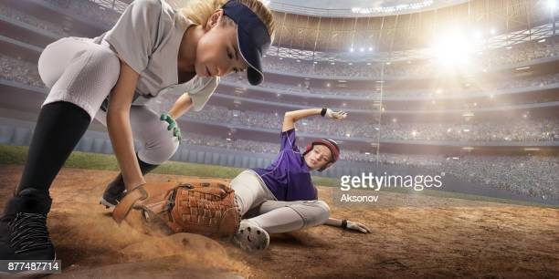 Softball female players on a professional arena. Baseball 3rd base slide